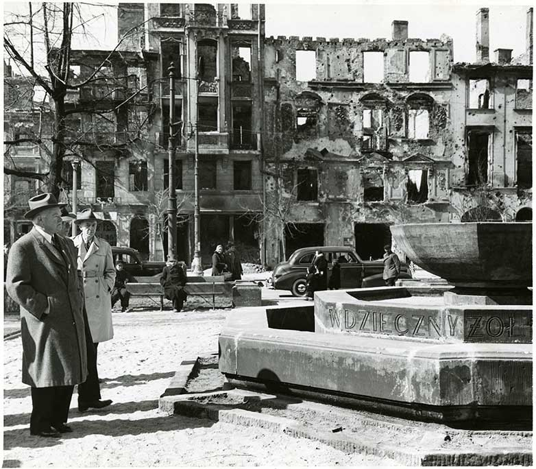 Herbert Hoover views the ruins of Warsaw while standing in