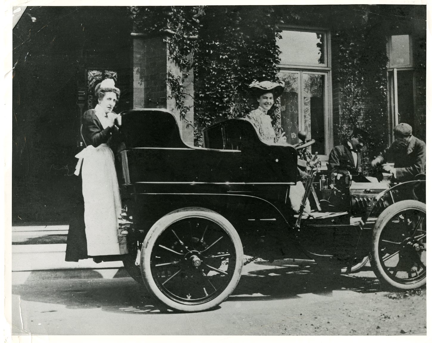 London, the first Hoover automobile, Mrs. Hoover behind the wheel and Mr. Hoover checking the engine. 1903