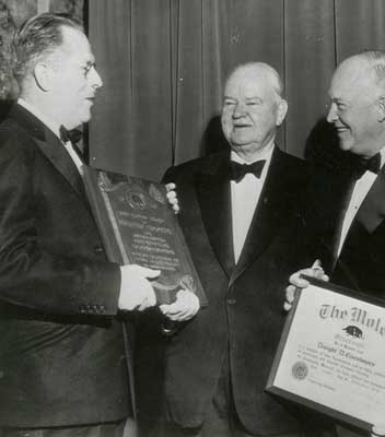 Herbert Hoover is presented with an award for public service and contributions to construction by the Moles.