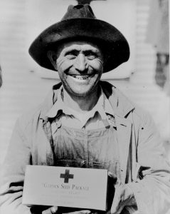 A farmer poses with his Red Cross seed package.